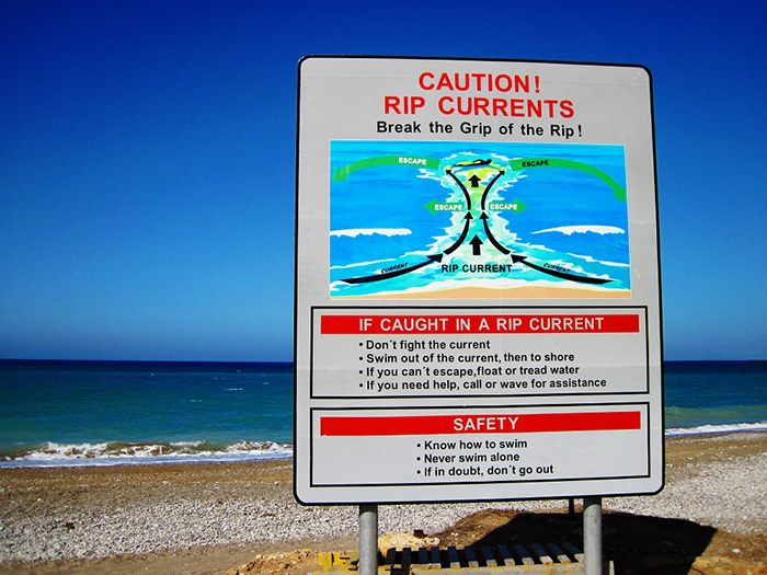 rip currents caution showing the things to do when caught in a rip current and other safety tips at the beach