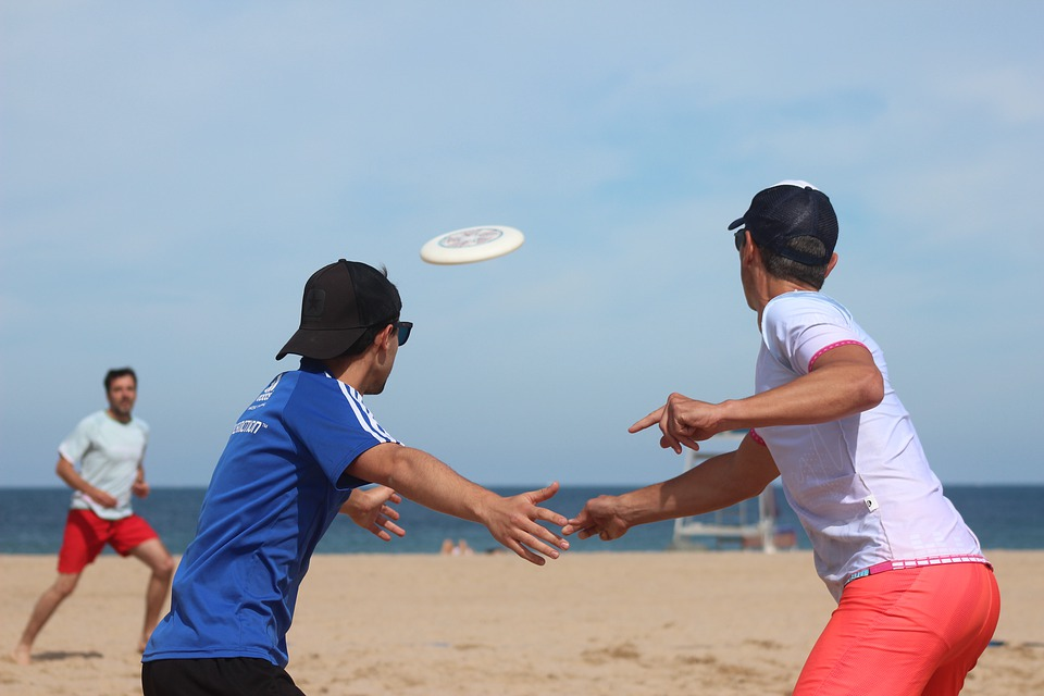 three men playing frisbee at the beach